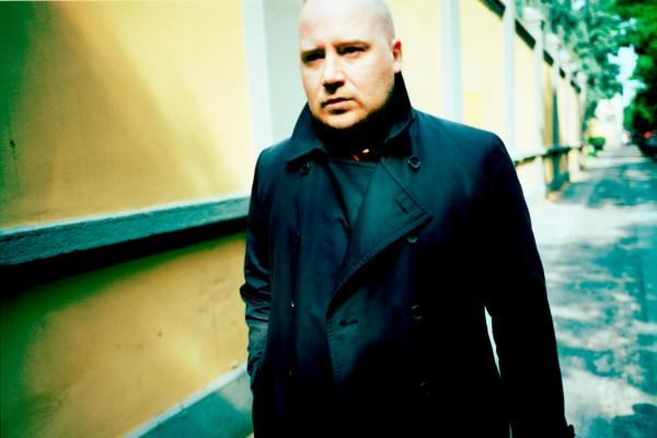 Johann Johansson walking down sunny street wearing black coat, yellow wall behind him