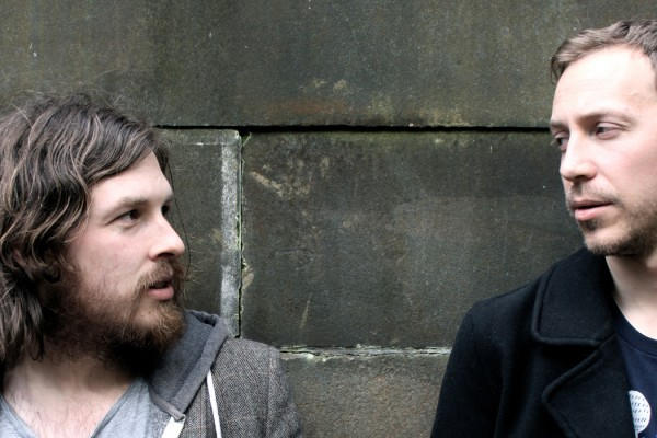 Graveyard Tapes, the two band members looking at each other with a brick wall behind