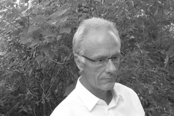 Jürg Frey, composer in white shirt stood with hedge in background, black and white