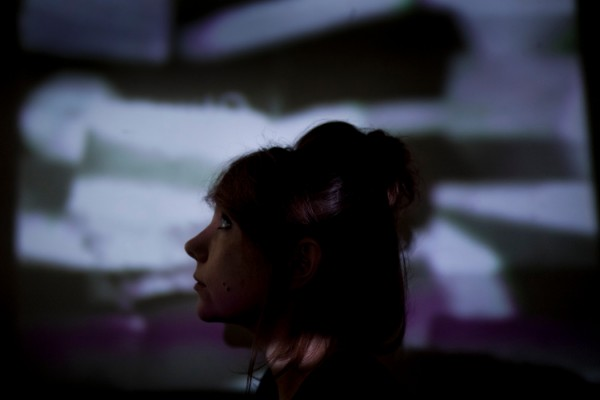 Poppy Ackroyd by Kat Gollock, artist silhoette in foreground with film projected behind her