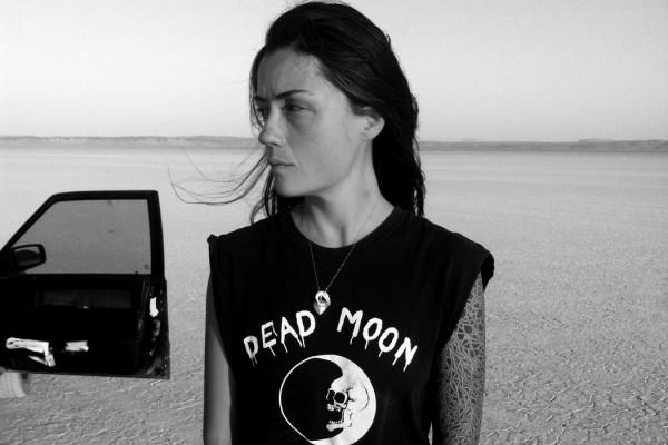 Grouper - Ruins, musician stands in a desert wearing a black 'Dead Moon' t-shirt, open car door behind her