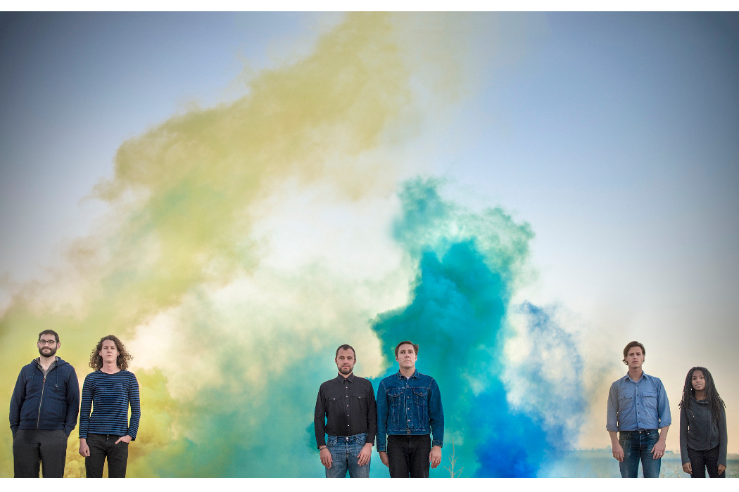 Balmorhea, photo by Pedro Anguila, band standing in pairs with blue and yellow smoke behind them