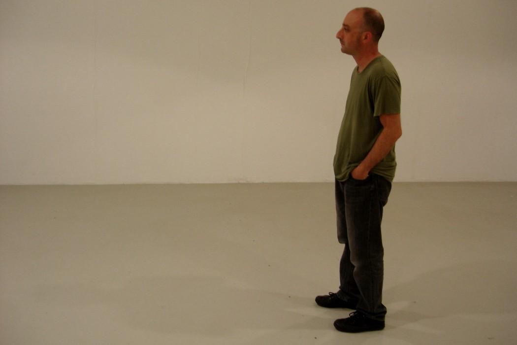 Cem Güney, composer standing in white room