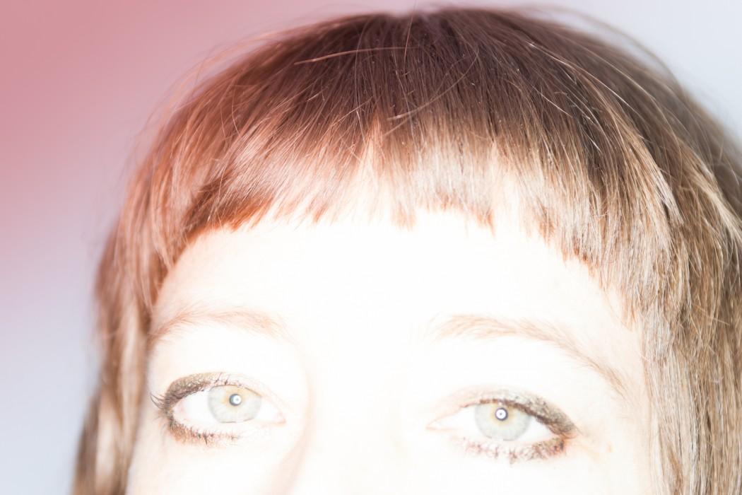 Jasmine Guffond - Yellow Bell, closeup of artist's eyes and fringe under bright light, photo by Black Flamingo
