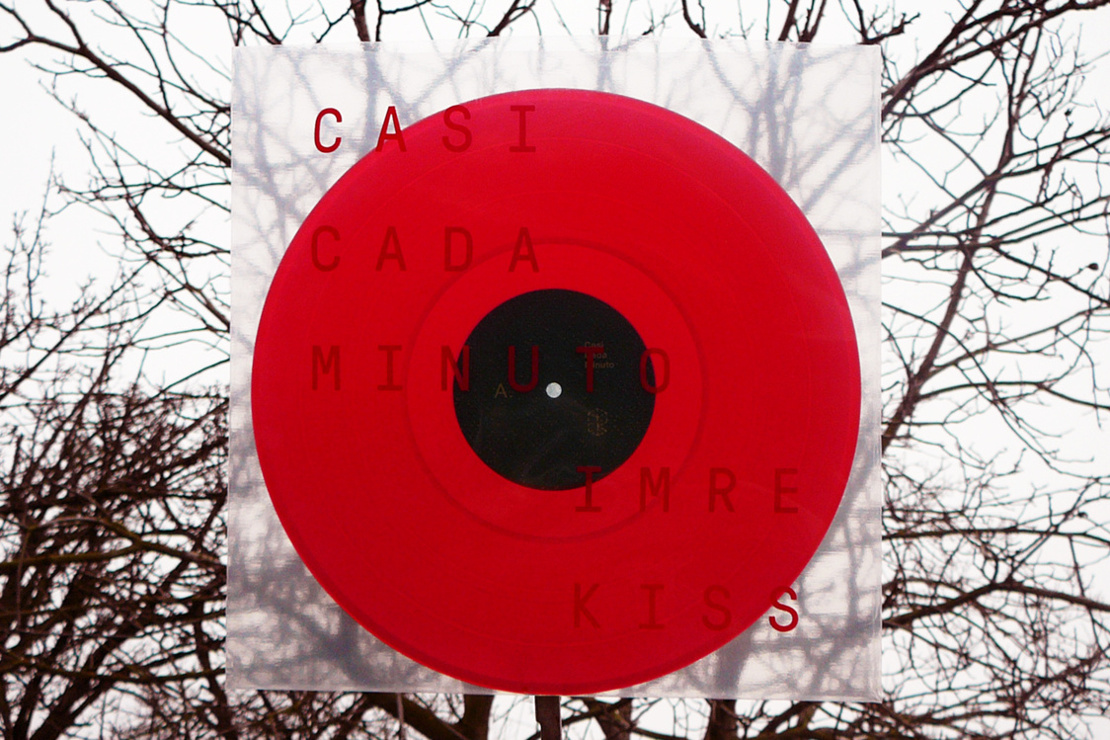 Proto Sites release artwork - poppy-red vinyl record against leafless trees