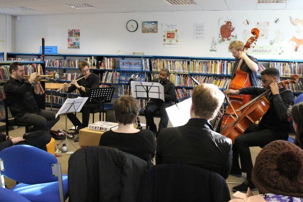 for-Wards performance Aston Library, five musicians performing surrounded by bookshelves