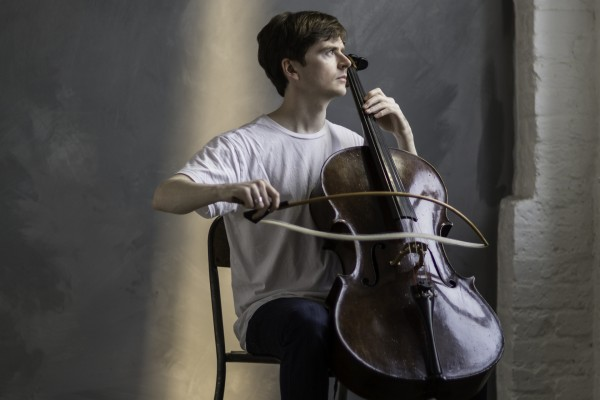 Oliver Coates, cellist sat in church or temple-like stone building