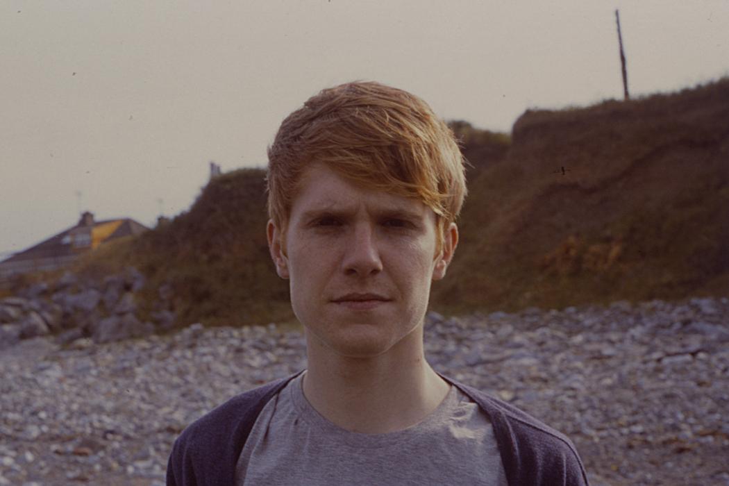 Paul McGuire - Sleep Spindles, close up of artist stood on grey pebble beach
