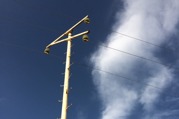 nula.cc - telegraph pole against blue sky with white fluffy cloud