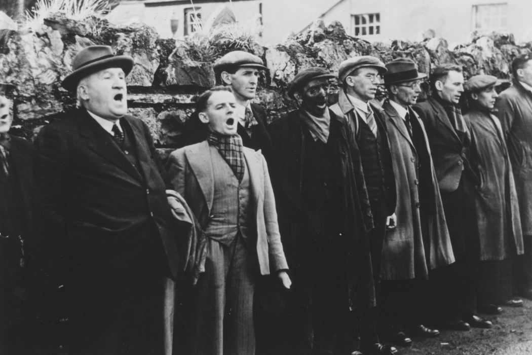 Humphrey Jennings, The Silent Village, men stood shouting or singing in a 1940s British village