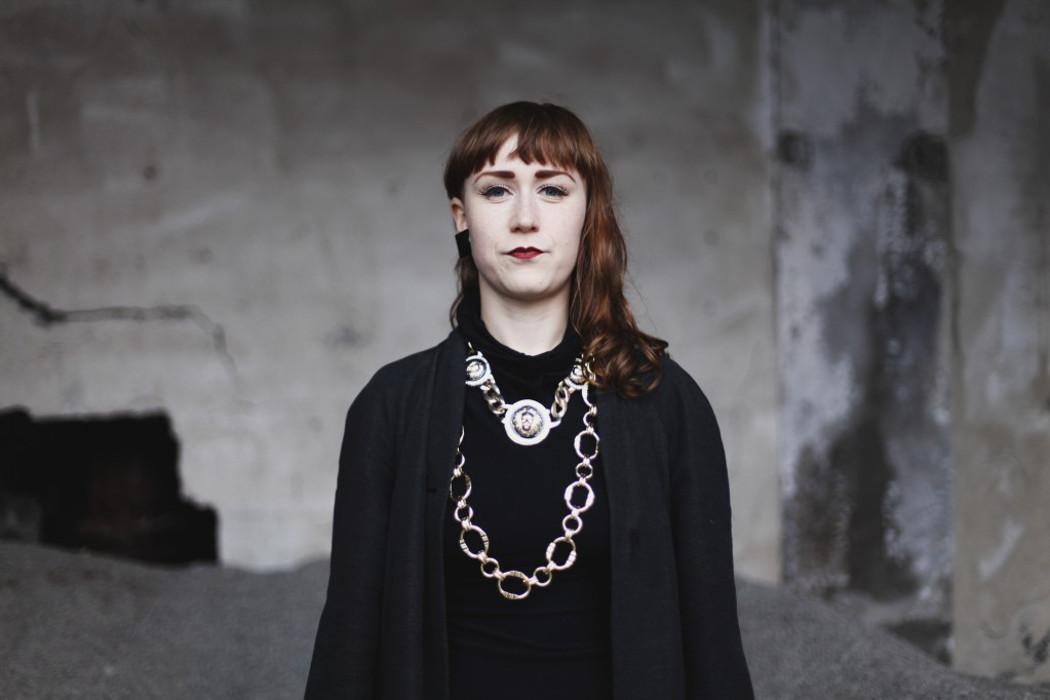Marta Forsberg, artist dressed in black against crumbling white background