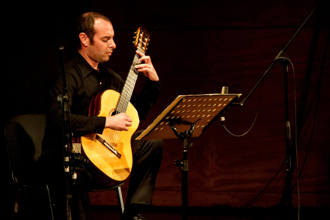 Frey / Alvear - guitarist, alone, photo of Alvear playing guitar in a concert