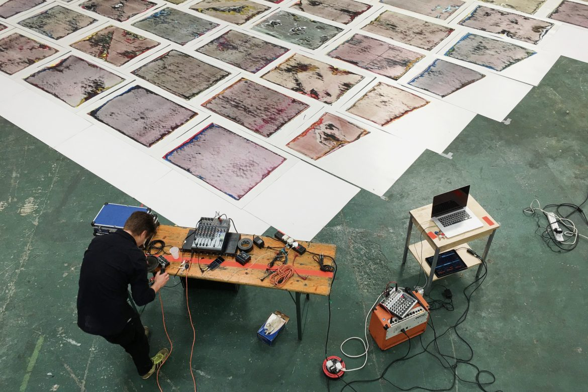 Idle Chatter, overhead view of large room with painted tile artworks on the floor, table with experimental electronic music gear, musician
