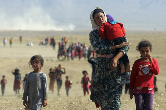 Displaced people from the minority Yazidi sect, fleeing violence from forces loyal to the Islamic State in Sinjar town, walk towards the Syrian border on the outskirts of Sinjar mountain near the Syrian border town of Elierbeh of Al-Hasakah Governorate in this August 11, 2014 file photo. The Islamic State, which had declared a caliphate in parts of Iraq and Syria, prompted tens of thousands of Yazidis and Christians to flee for their lives during their push to within a 30-minute drive of the Kurdish regional capital Arbil.    REUTERS/Rodi Said/Files  (IRAQ - Tags: POLITICS CIVIL UNREST TPX IMAGES OF THE DAY)   ATTENTION EDITORS - THIS PICTURE IS PART OF PACKAGE '30 YEARS OF REUTERS PICTURES'  TO FIND ALL 56 IMAGES SEARCH '30 YEARS' - RTR4PFCZ