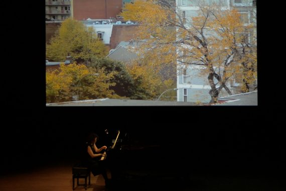 Eve Egoyan playing a grand piano with a projected image of autumn trees and buildings behind her
