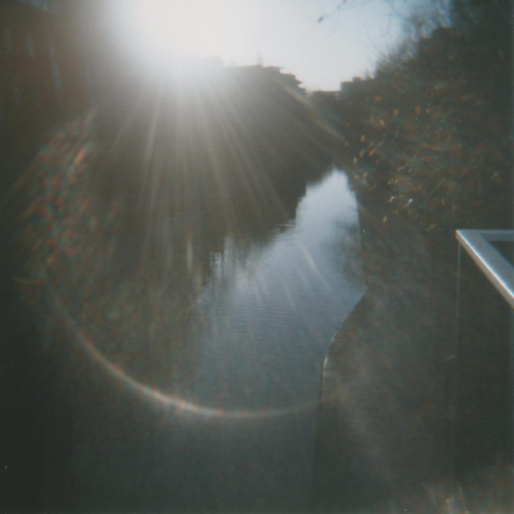 Canal, photo from a bridge looking down on a dark canal, strong lens flare