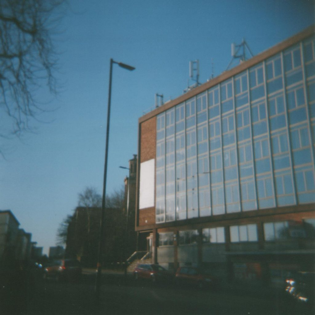 Office Block, modernist office block with road in foreground and church steeple in background