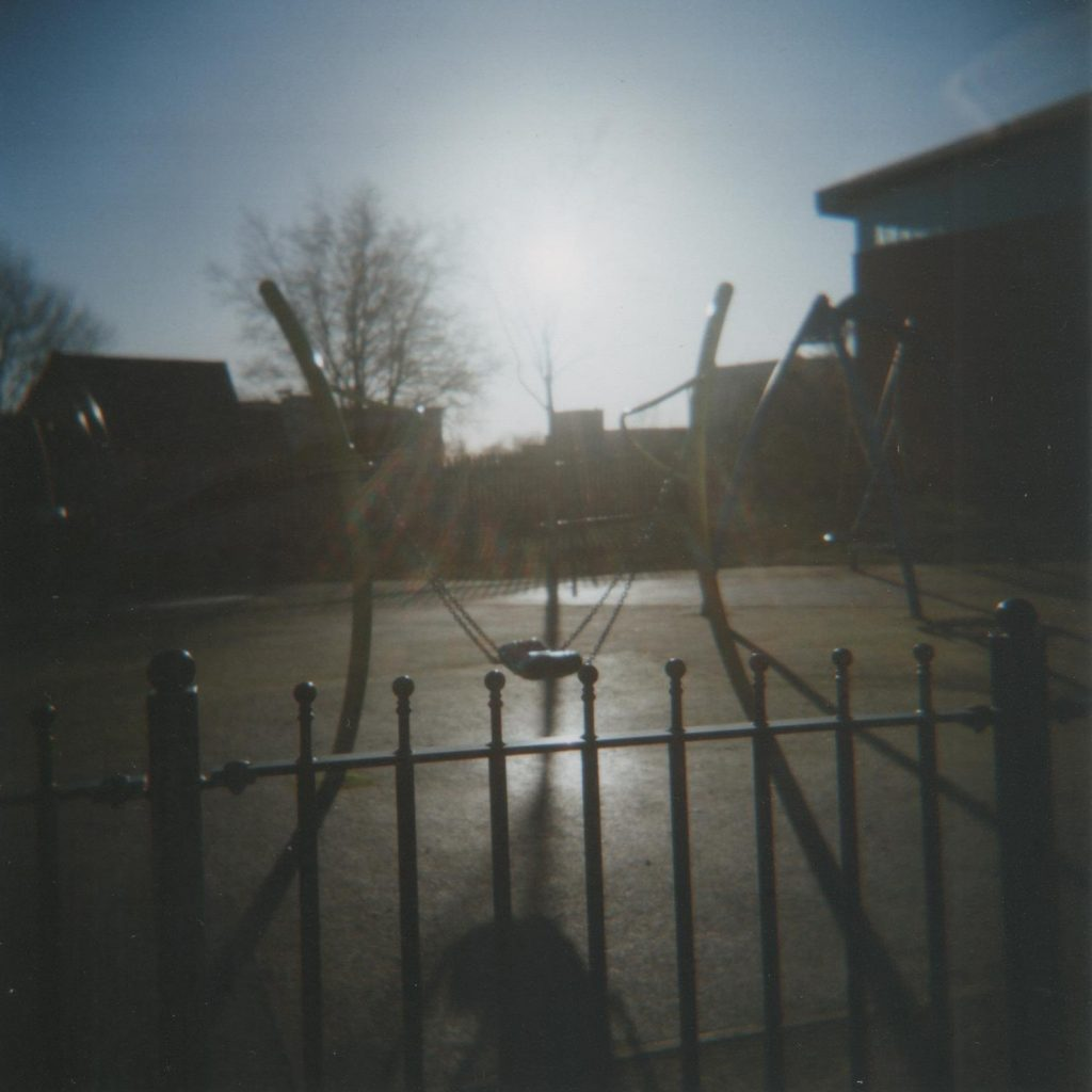 Playground, silhouette of fence and swing in the sunlight