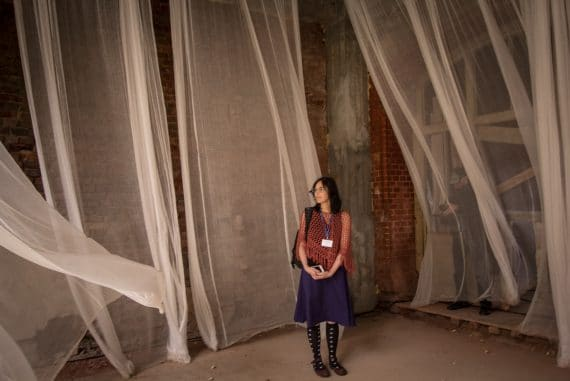 Olivia Block's Cinematic Deceptions - artist stood in Open Air installation, white net curtains floating against brick walls