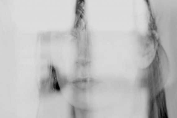 Jana Irmert - End of Absence, vague impression of artist's face reflected in glass