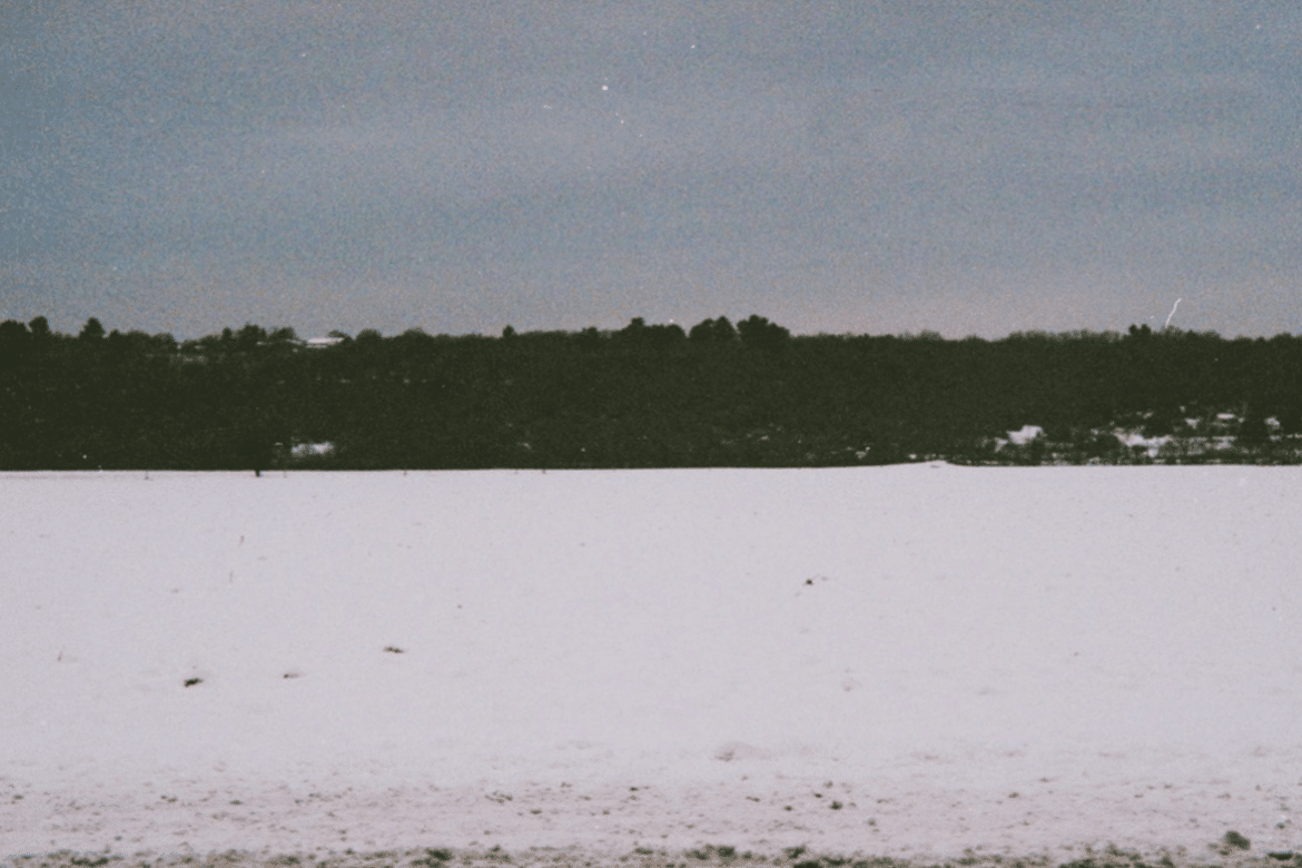 Clara de Asís + Bruno Duplant - L'inertie, dark shore seen from the middle of a frozen snow-covered lake, cobalt sky