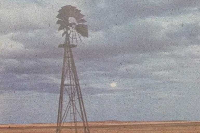 Mark So - And suddenly from all this there came some horrid music, old photograph of a metal windmill against a cloudy sky and flat prairie landscape