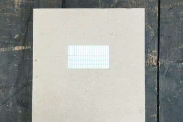 Ryoko Akama - places and pages, a large grey notebook on a dark wooden surface