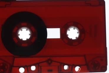 Grisha Shakhnes - The distance between a word and a deed, closeup of a translucent dark red cassette tape