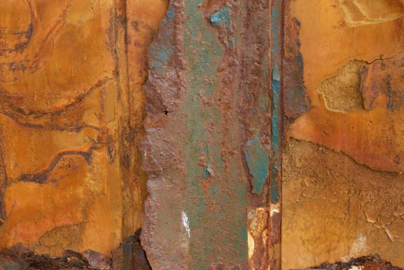 Jake Muir - Acclimation, closeup of rusted orange and blue industrial surfaces that resemble sheets of rock