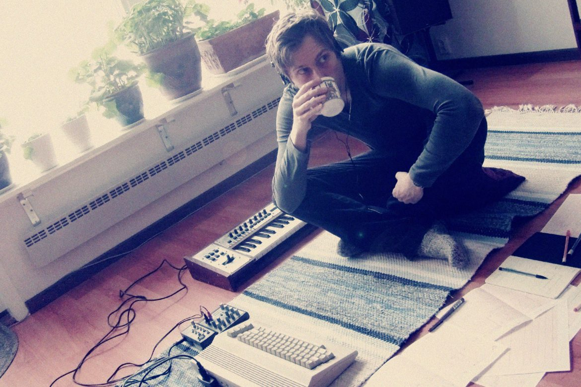 Marcus Fjellström sat on a rug in a living room drinking from a mug, surrounded by audio equipment, notebooks, and indoor plants