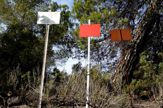 Kate Carr - From A Wind Turbine To Vultures (and back), three metal signs on a hillside.