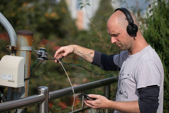 Simon Whetham - Open and Closed Circles, artist outdoors recording sounds from electrical wires.