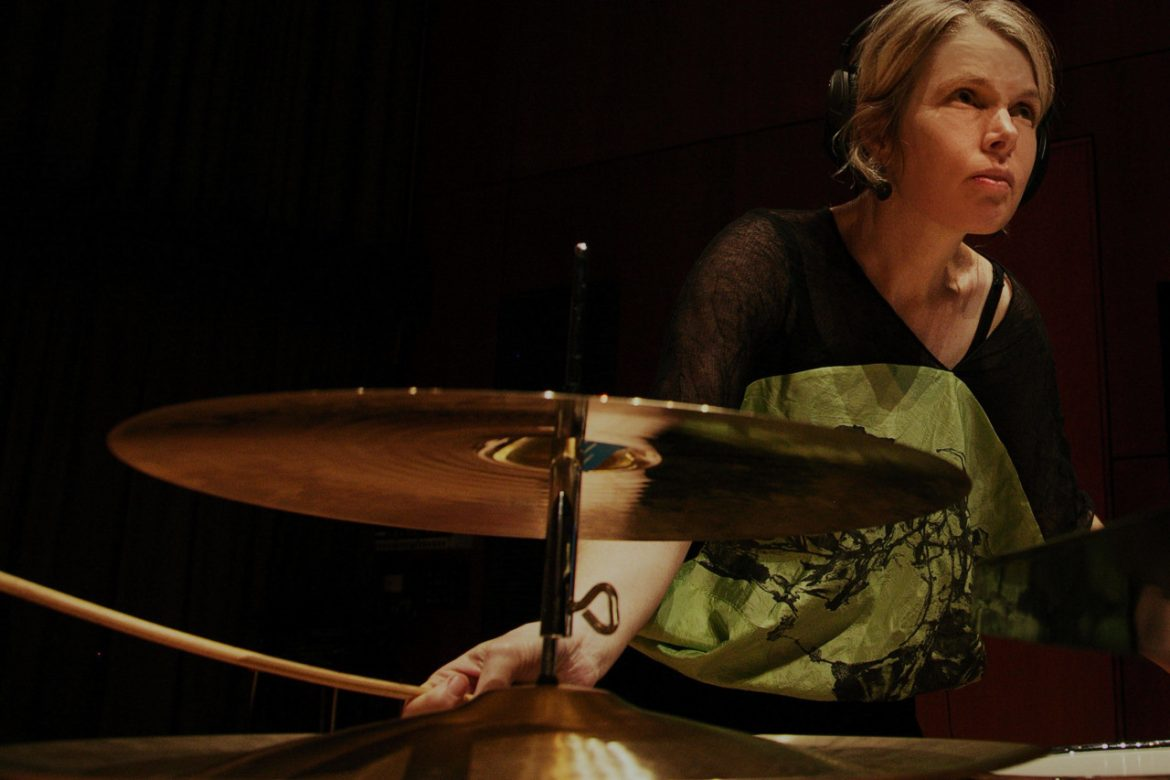 Vanessa Tomlinson - The Space Inside, artist with headphones playing cymbals.