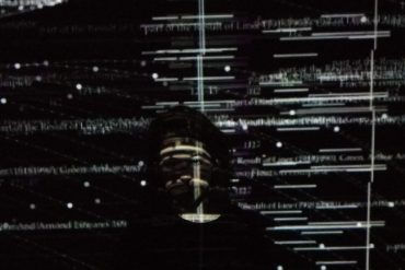 Laura León, artist against a black background overlaid with projections.