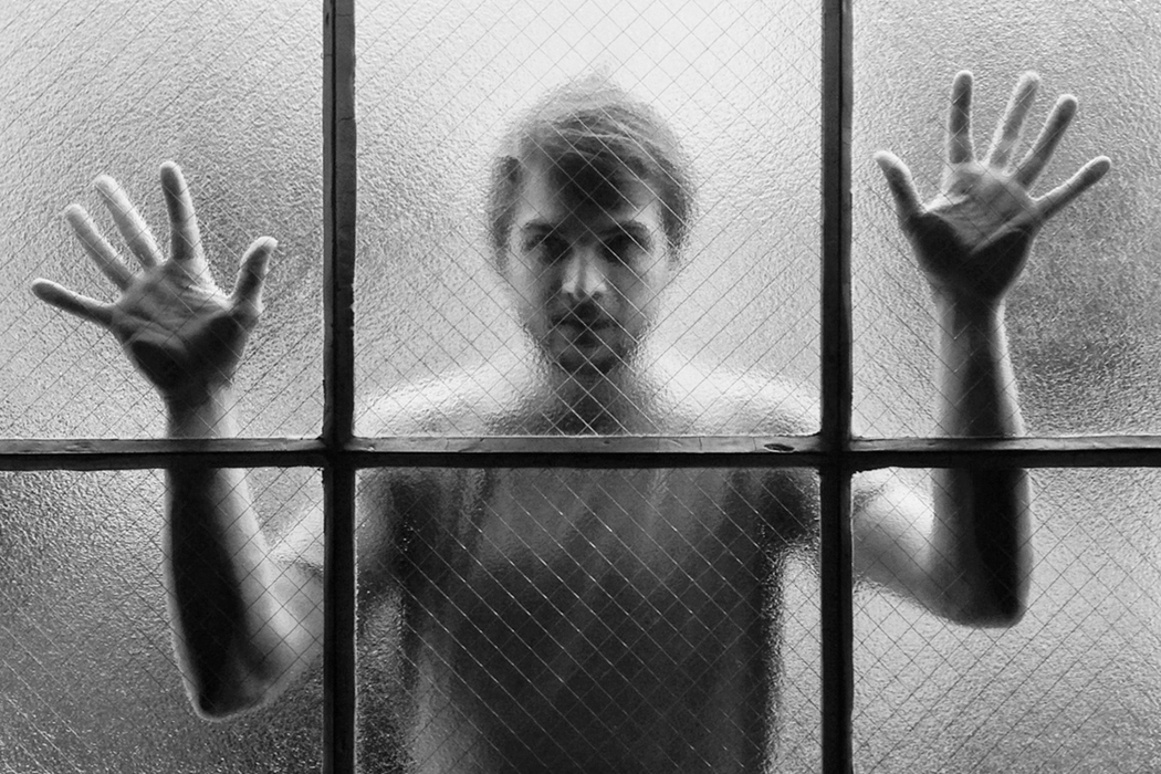 Nils Frahm portrait by Michal O'Neal, Frahm looking through frosted window with hands on glass