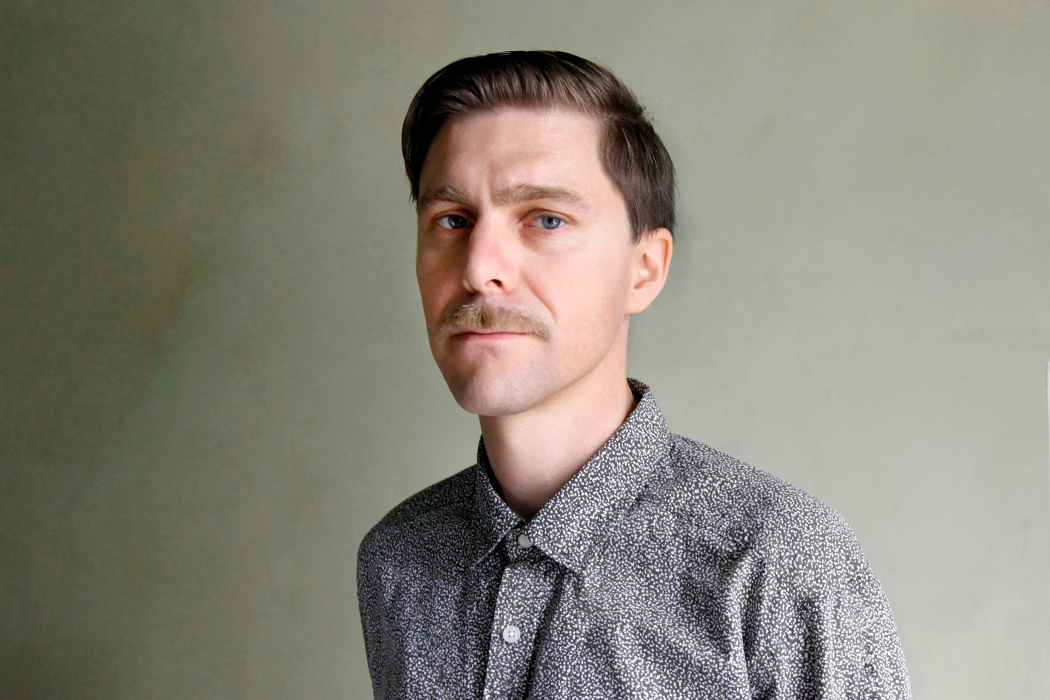 Andrea Belfi - Natura Morta, artist with moustache and blue shirt looking straight at camera, plain background