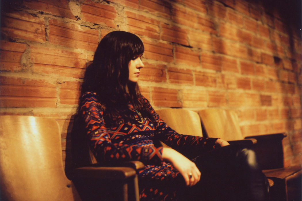 Noveller, photo by Alex Marks, artist lounging on a sofa against a brick wall