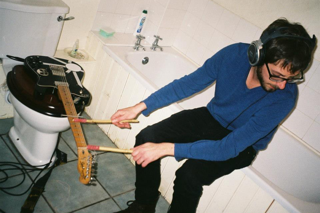 Ex-Easter Island Head - Two Comissions for Cassette, musician playing a guitar with mallets in a bathroom