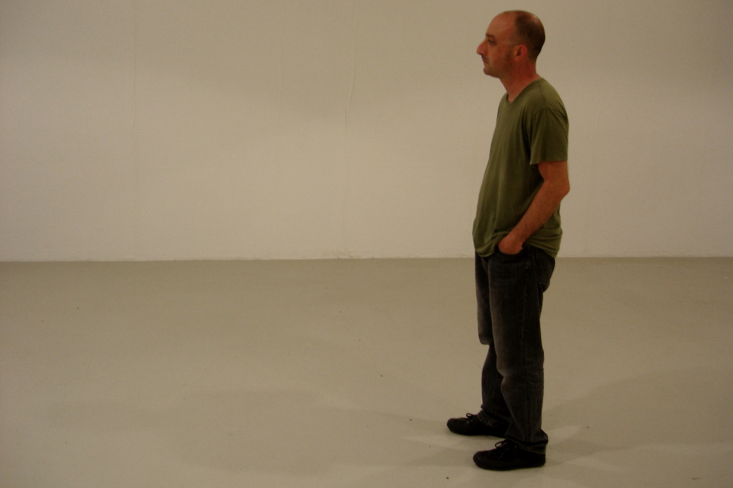 Cem Güney, composer standing in white room