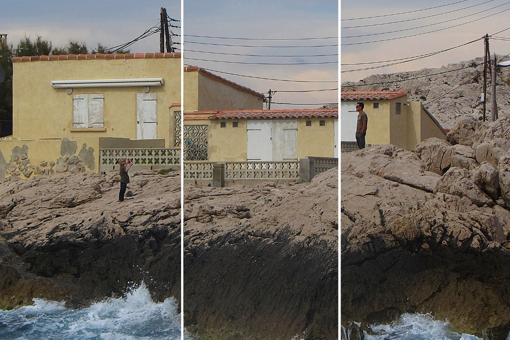Kate Carr - Fabulations, two people stood on rocky shoreline with yellow houses behind, image split vertically into three slightly off-set sections