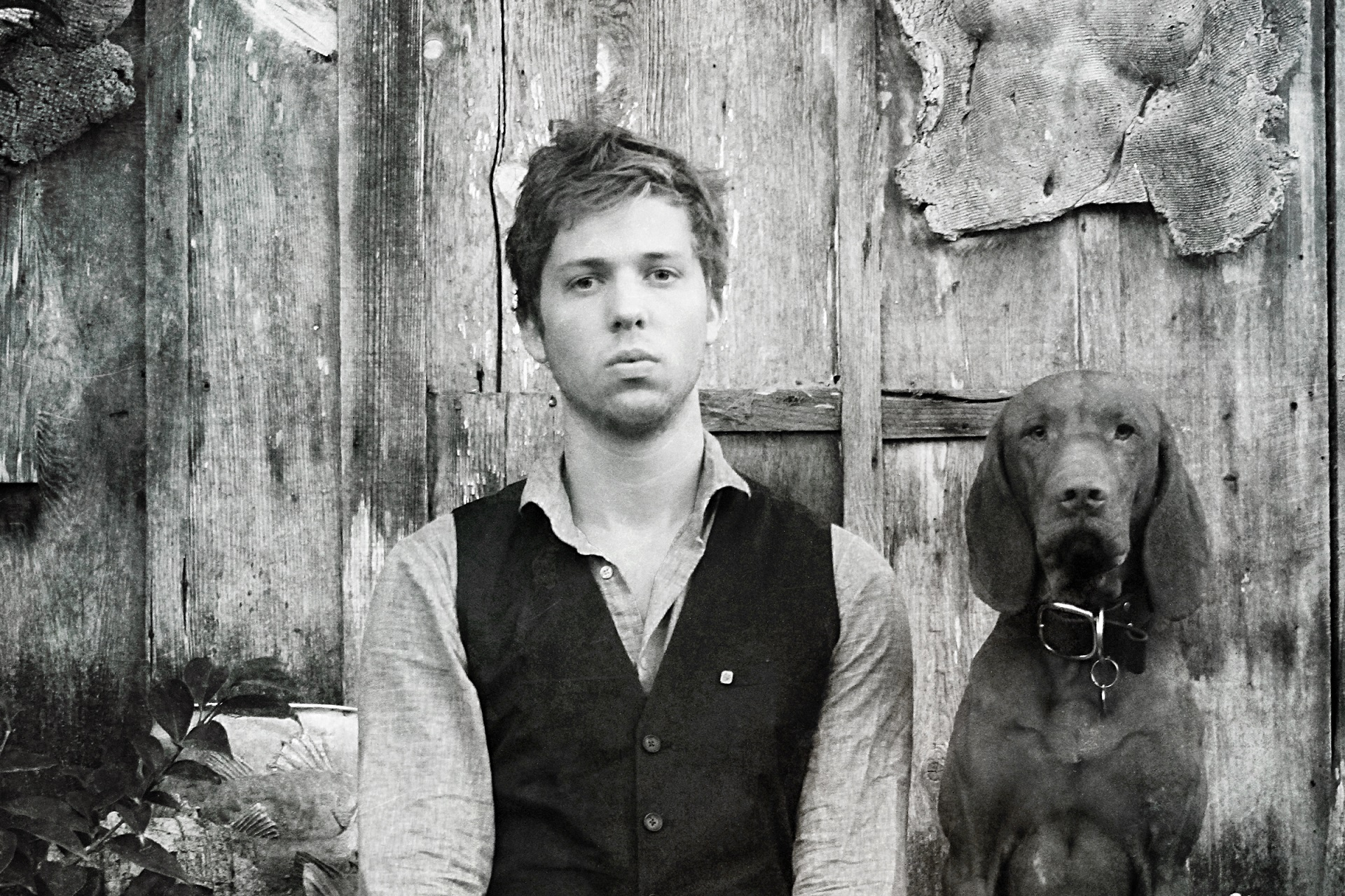 William Ryan Fritch, artist sat in front of wooden wall with his dog