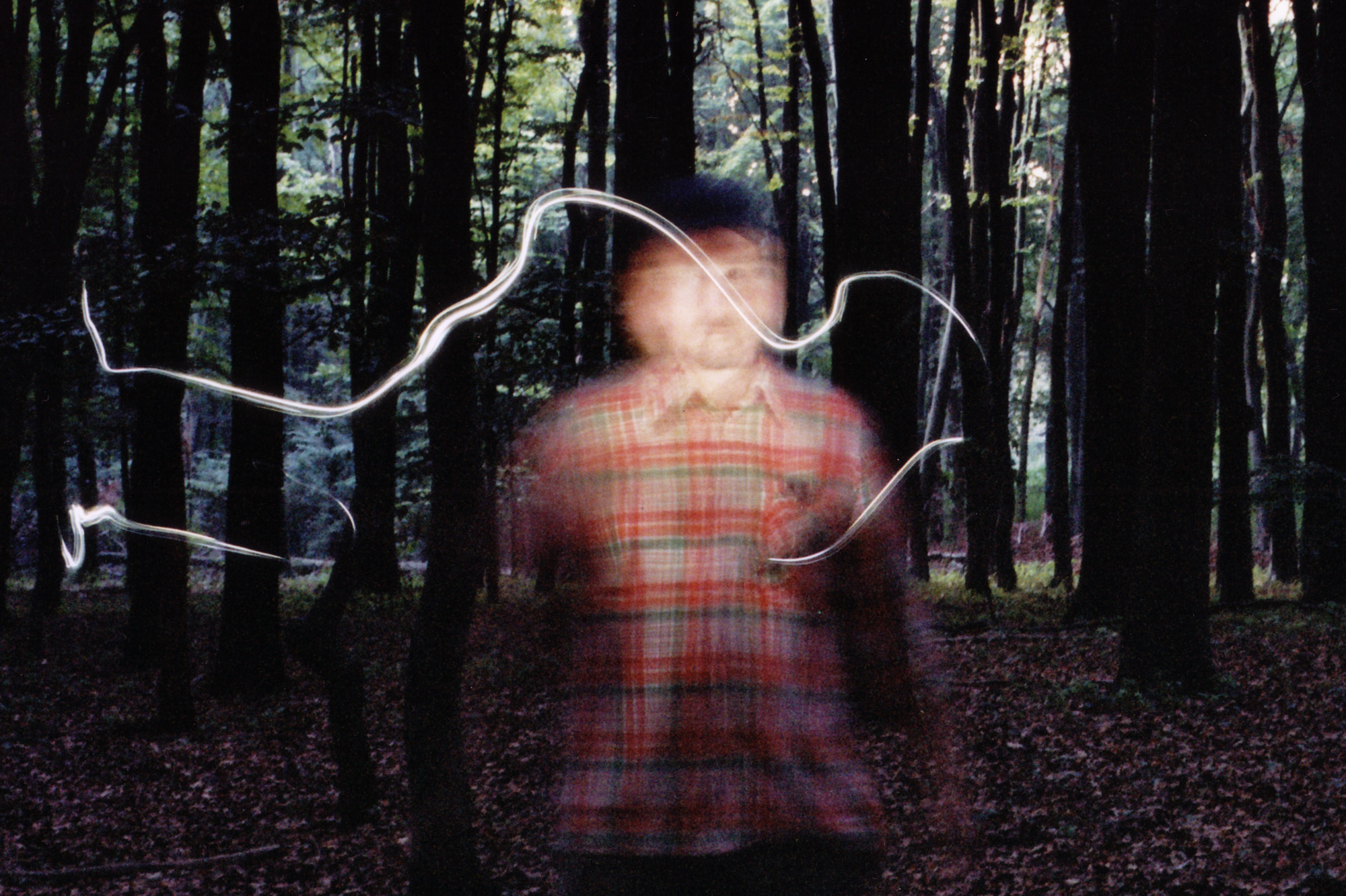 Black To Comm by Renate Nikolaus, motion-blurred photograph of artist stood in forest with light waves