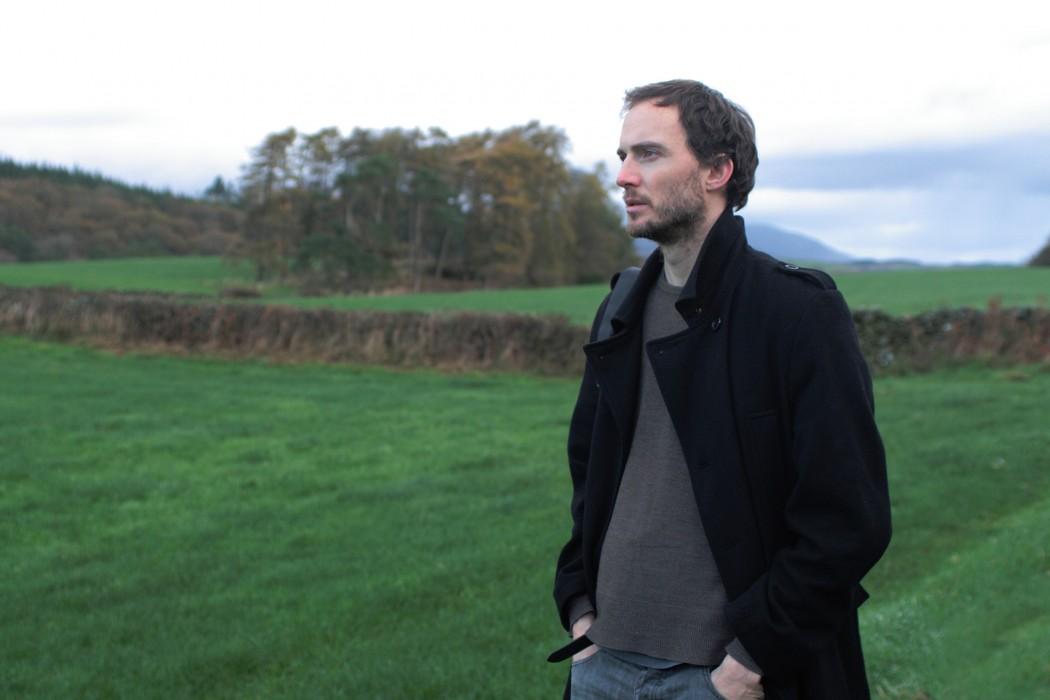 Richard Skelton, artist in black coat stood in field