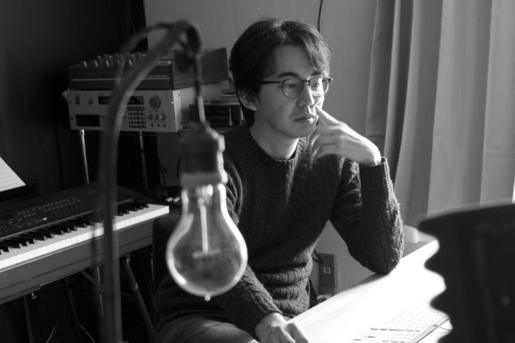 Marihiko Hara, composer sat at desk with piano, synths, and lightbulb