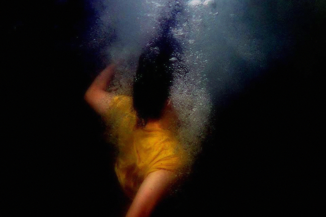 Kate Carr - It Was A Time Of Laboured Metaphors, woman in bright yellow t-shirt underwater, black background