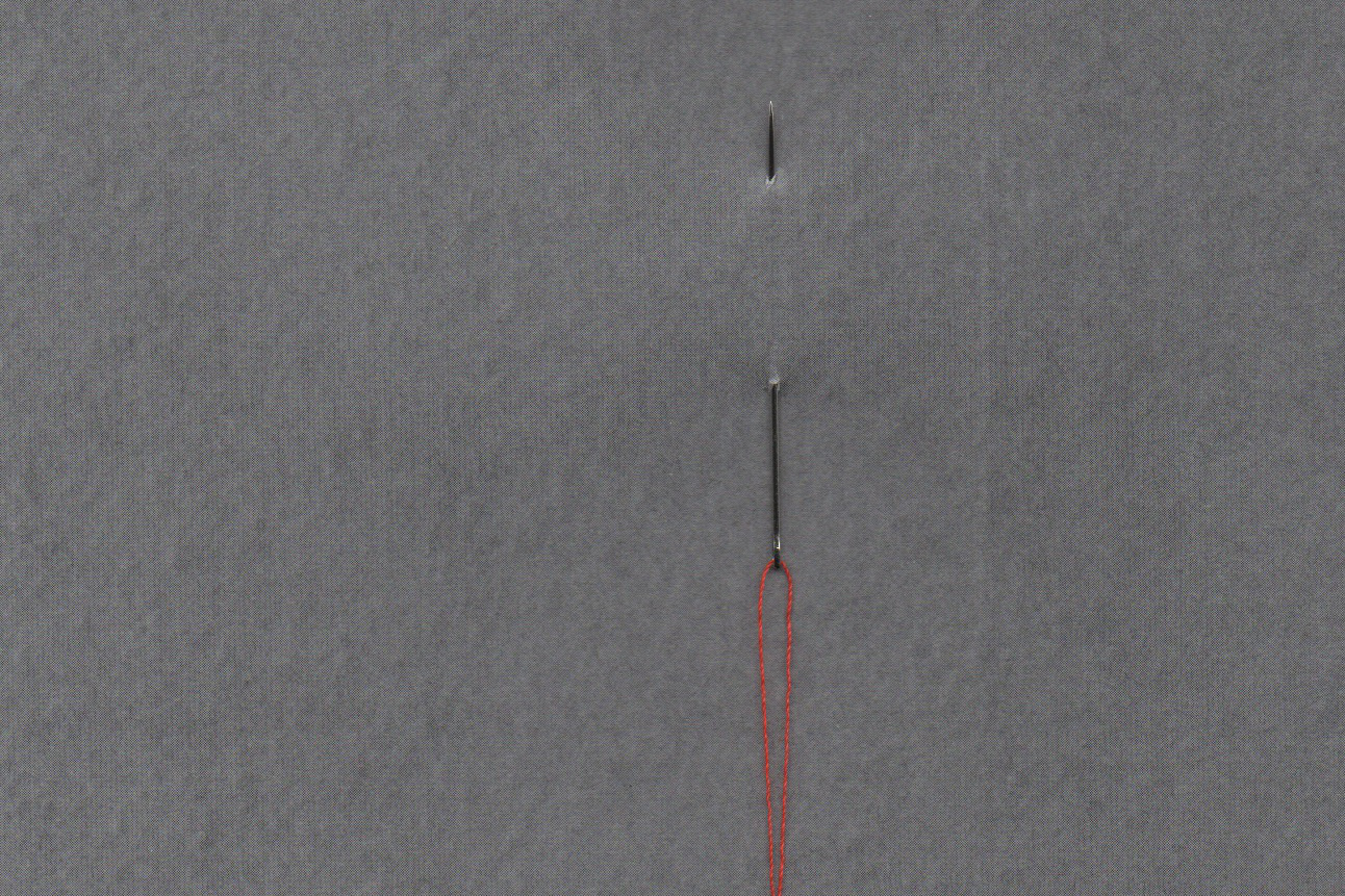 Sarah Hennies - Gather and Release, needle with red thread piercing a grey sheet of paper