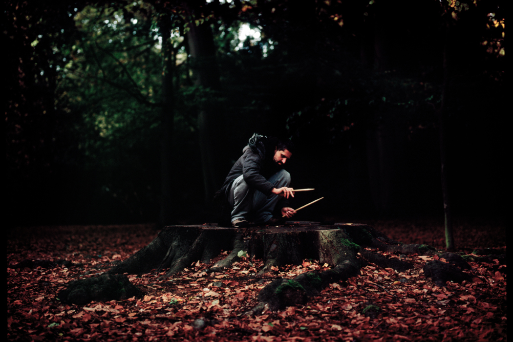 Eric Thielemans - Aural Mist, artist crouched on a tree trunk in a forest, playing it with drumsticks