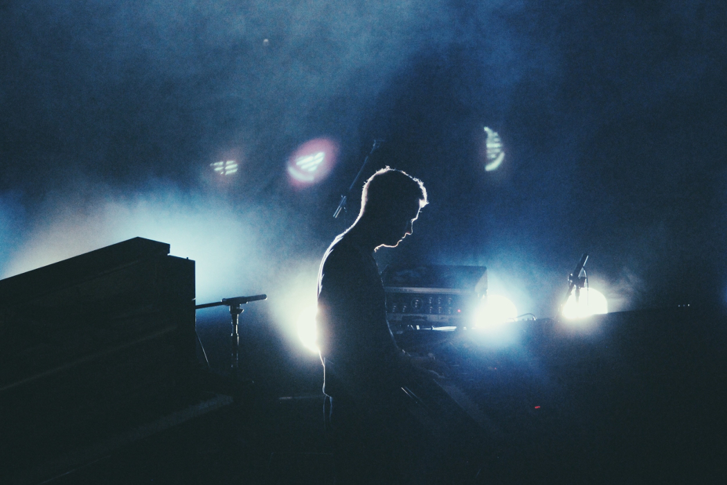 Alex Kozobolis - Weightless, silhouette of musician playing piano on a dark stage with stage lights in the background