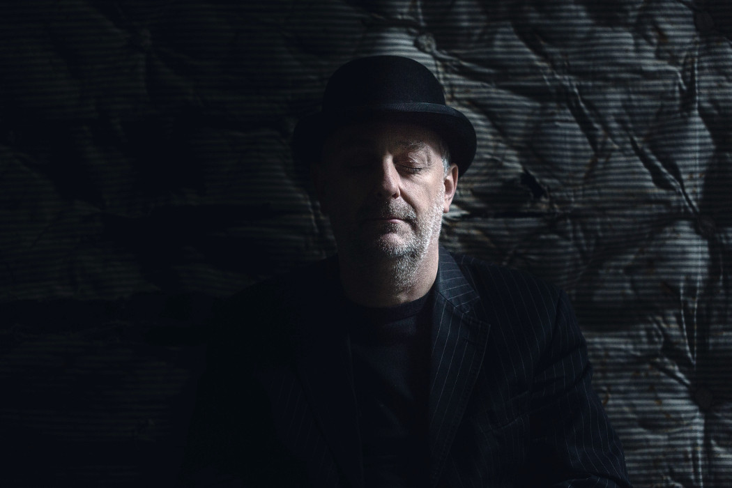 Antonymes - Delicate Power (In The Hands of Others), artist wearing black suit and bowler hat photographed against a darkly lit mattress, eyes closed