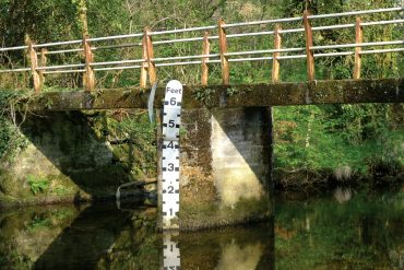 Simon Scott - Floodlines, bridge over water with a water height measuring stick